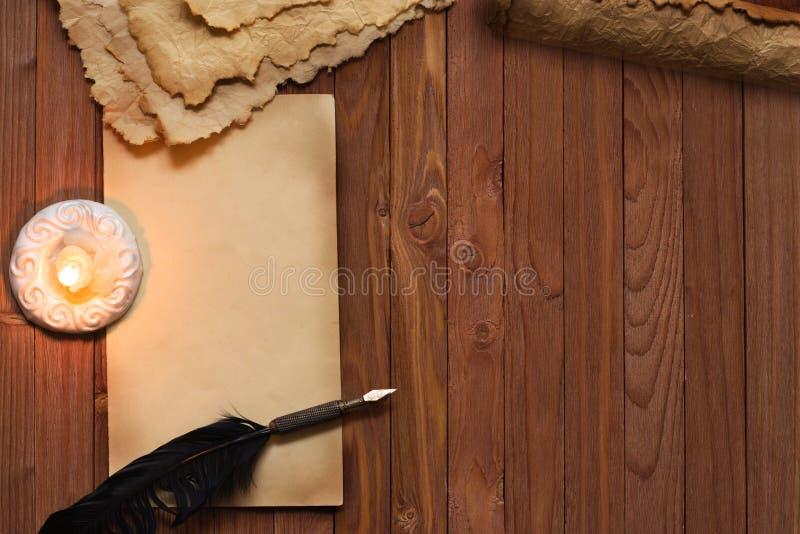 Czysty prześcieradło stary papier, piórko i płonąca świeczka, zdjęcia royalty free