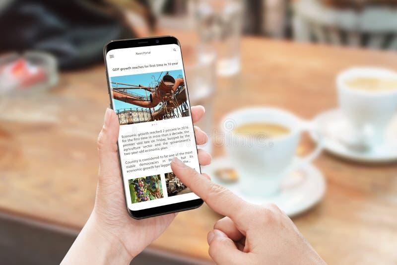 Czyta artykuł prasowego z mądrze telefonem Wiadomości wrotna strona internetowa z biznesową informacją obrazy royalty free