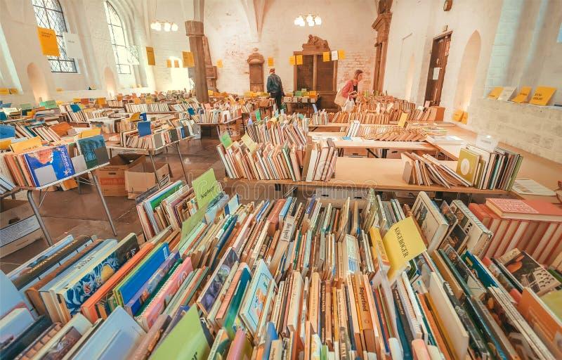 Czytelnicy leaf przez stron antykwarskie książki przy sklepem w dziejowym kościół zdjęcia royalty free