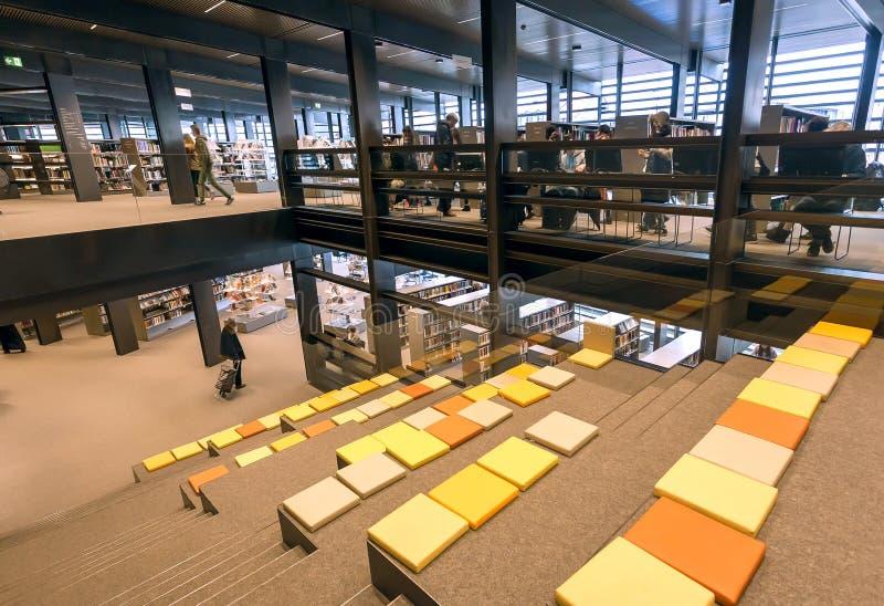 Czytelnicy ogląda książki wśrodku nowej biblioteki publicznej De Krook z półka na książki i holem fotografia royalty free