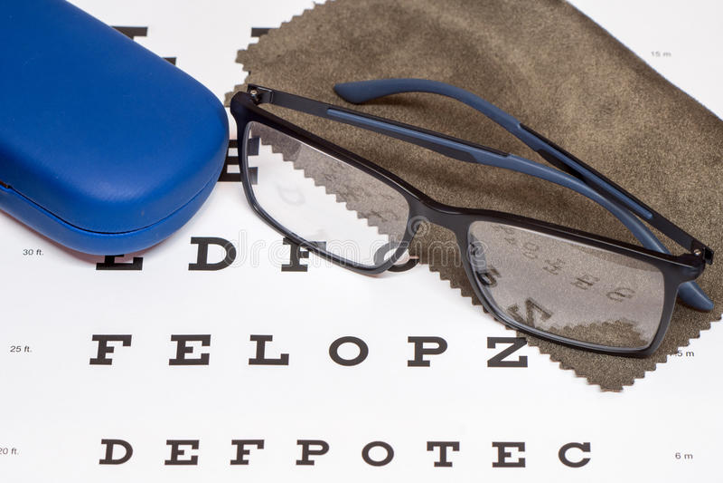 Czytelniczy czarni eyeglasses, brown microfiber cleaning płótno i błękitna ochronna skrzynka na białej oko mapie, obrazy royalty free