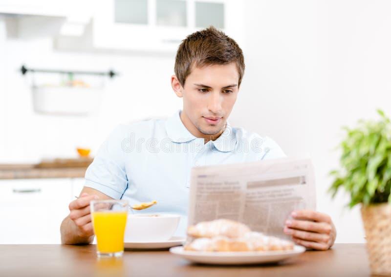 Czytelniczy mężczyzna je lekkiego śniadanie w kuchni zdjęcia royalty free