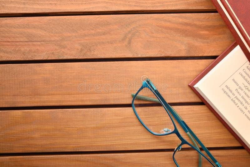 Czytelniczy szkła na drewno stole z książka wierzchołkiem fotografia stock