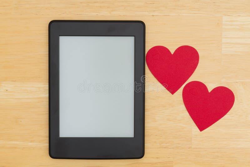 Czytelnik na drewnianym biurku z dwa sercami fotografia royalty free