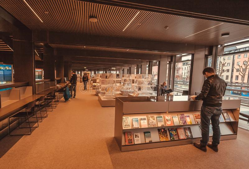 Czytelnika dopatrywania półka na książki z nowymi książkami wśrodku biblioteki publicznej De Krook z półka na książki zdjęcia stock
