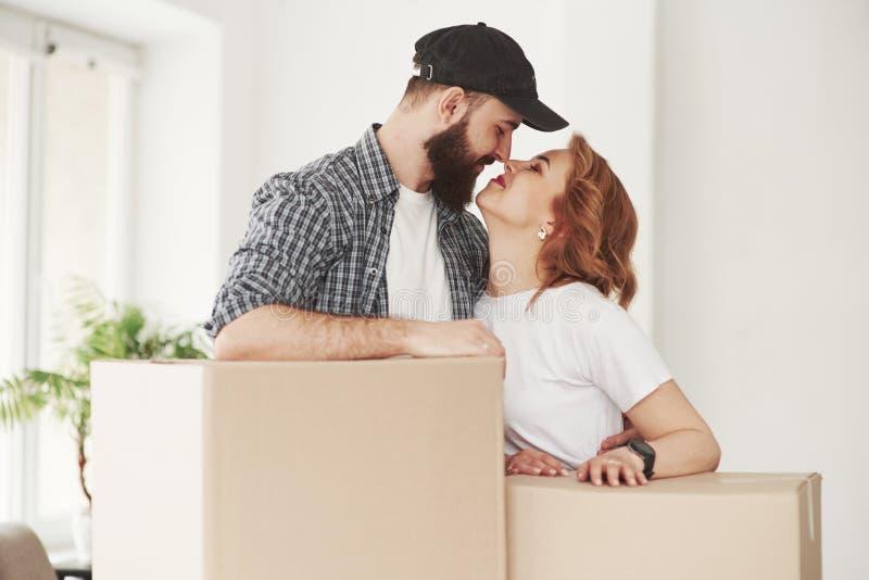 Dá-me um beijo Casal feliz juntos em sua nova casa Conceito de deslocação foto de stock royalty free