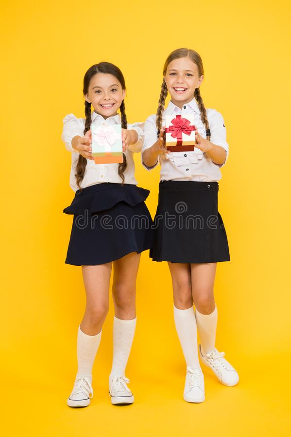Dándole a regalos a la gente amor Pequeños niños lindos que dan presentes en fondo amarillo Ni?as adorables fotografía de archivo libre de regalías
