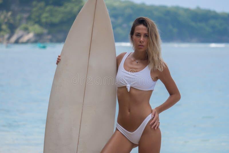 Dünnes erwachsenes Mädchen im weißen Bikini, der mit Surfbrett auf Hintergrund der Ozeanbucht aufwirft lizenzfreie stockfotos