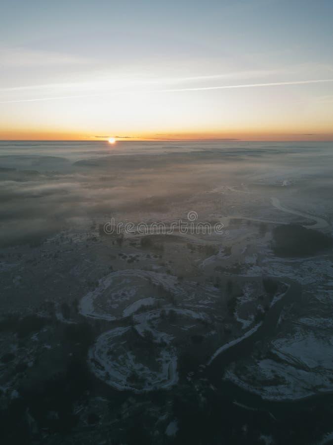 Dämmerung über dem gefrorenen Fluss, Nebel zwischen den Bäumen, Bündel Nebel stockfotos