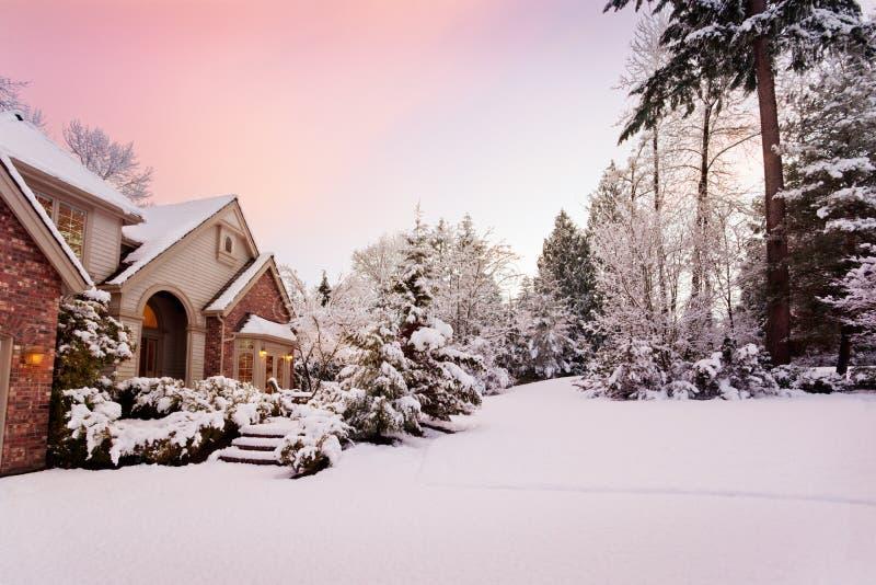 Dämmerung über schneebedecktem Haus stockfotos