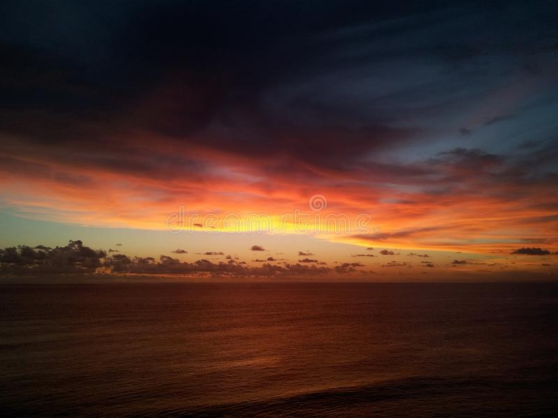 Dämmerung - Sonneneinstellung in dem Meer, das ein warmes gelbes Glühen und bläulichen Tönungshimmel zeigt lizenzfreies stockbild