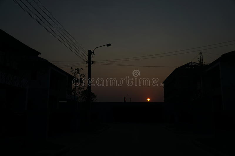 dämmerung Sonnenuntergang bis den Himmel ist mit dem Schatten des Dorfs rot lizenzfreies stockbild