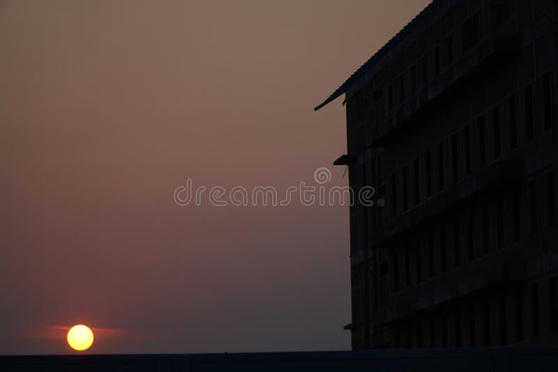 dämmerung Sonnenuntergang bis den Himmel ist mit Gebäudeschatten rot lizenzfreie stockfotos