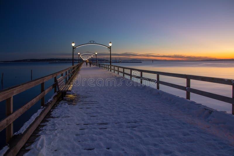 Dämmerungsweg auf schneebedecktem Pier, weißer Felsen nahe Vancouver stockfotografie