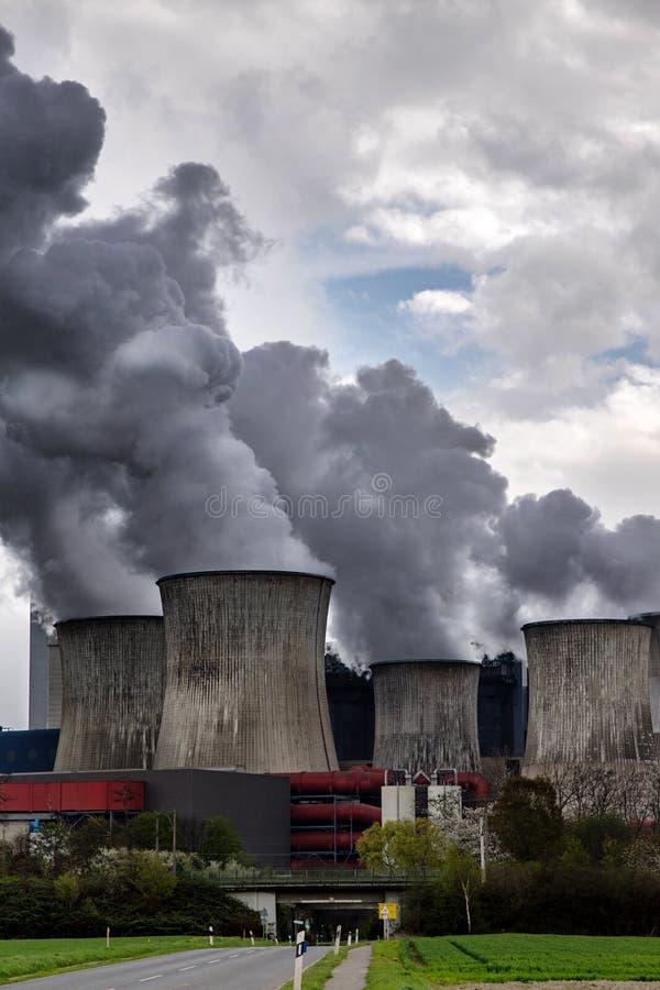 Dämpfen von Kühltürmen eines Kraftwerks mit dunkelgrauer Emission lizenzfreie stockfotografie