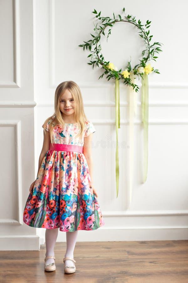 Długi mały uśmiechnięty dziewczyny dziecko w kolorowy sukni pozować salowy zdjęcia royalty free