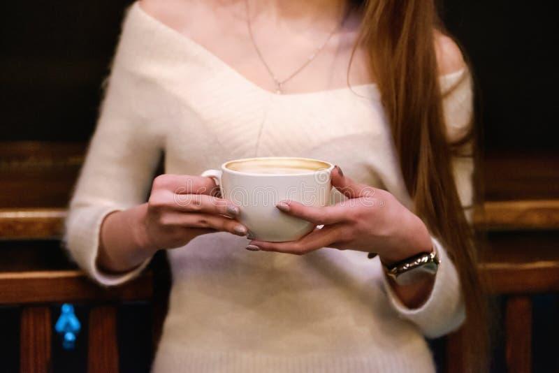 Długowłosa piękna dziewczyna w puloweru białych stojakach w sklepie z kawą przy drewnianym stołem z filiżanką, osamotniona dziewc obrazy stock