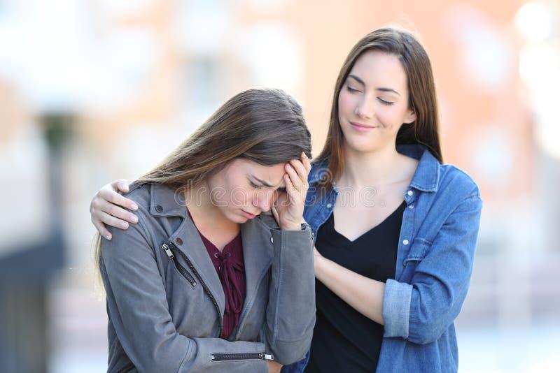 Dålig kvinna för hypokrit som tröstar hennes ledsna vän royaltyfria foton