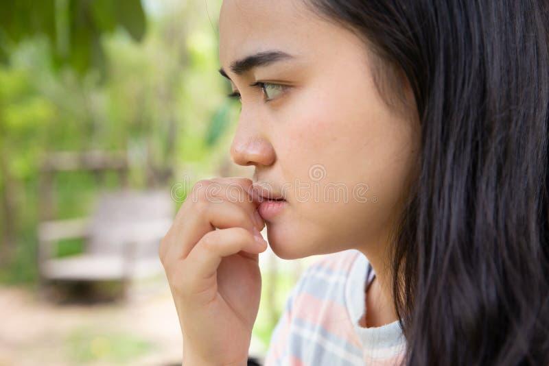Dålig tonårig nervös angelägen känsla för flicka och att spika att bita arkivbilder