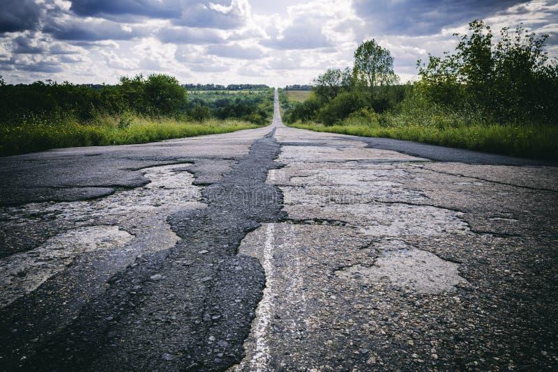 Dålig väg med skadad och bruten asfalt, svårt livbegrepp fotografering för bildbyråer