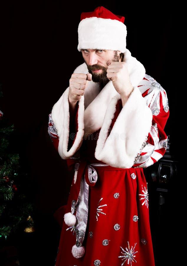 Dåliga brutala Santa Claus grep hårt om hans nävar, ordnar till för att slåss på bakgrunden av julgranen arkivbild