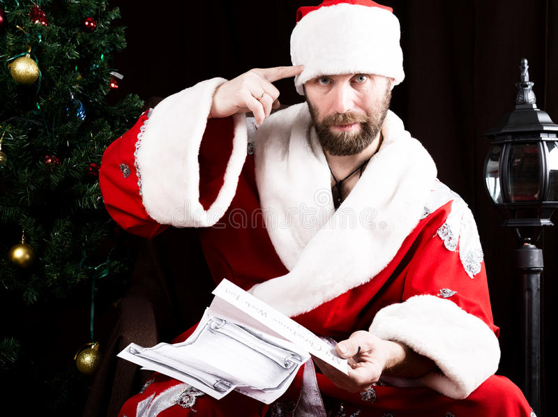 Dåliga brutala Santa Claus läser discontentedly brevet med önska, och vridningar fingrar på en tempel, på bakgrunden av royaltyfri bild