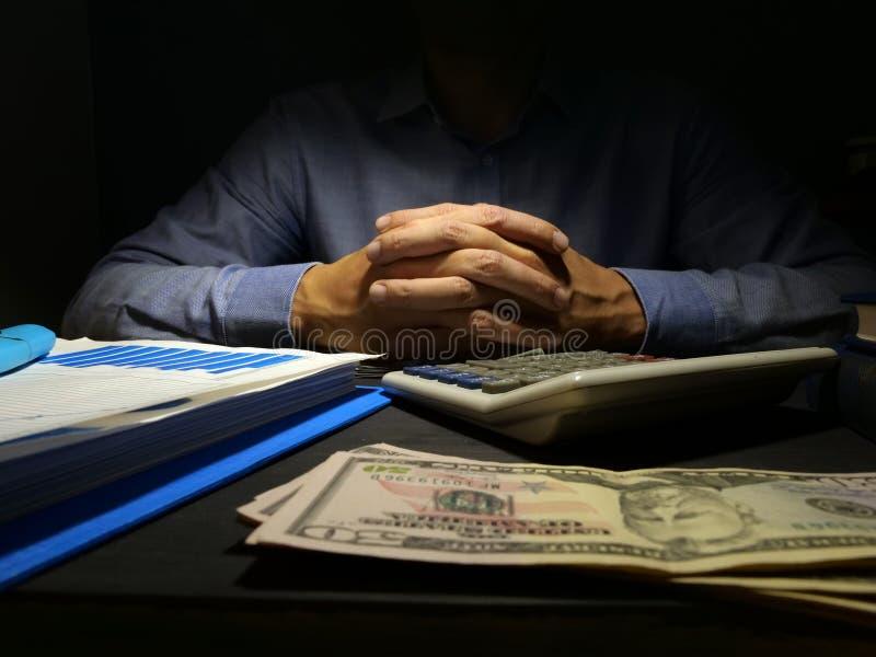 Dåliga kreditering eller avlöningsdaglån Man på skrivbordet och pengarna arkivfoton