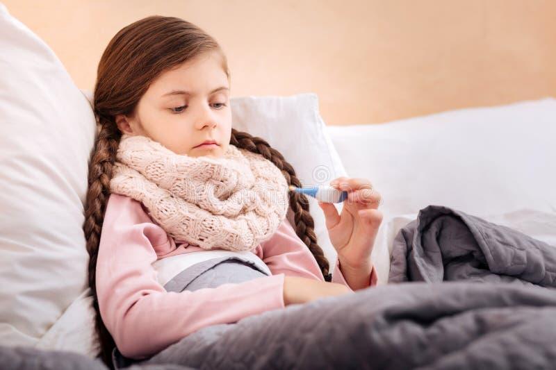 Dåligt barn som uppmärksamt ser på termometern arkivbild