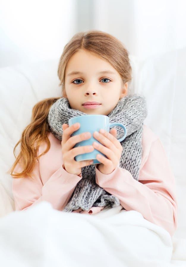 Dåligt flickabarn med koppen av varmt te royaltyfria foton