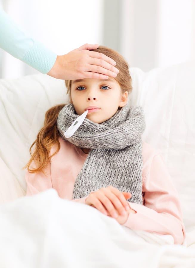 Dåligt flickabarn med termometern och att bry sigmodern fotografering för bildbyråer