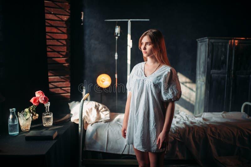 Dåligt kvinna i sjukhus, droppande och säng på bakgrund royaltyfri foto