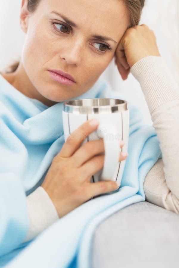 Dåligt kvinna med koppen av den varma drycken arkivfoton