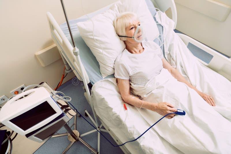 Dåligt kvinna med medicinsk utrustning för hjärtahastighet och respiratorisk service royaltyfri bild