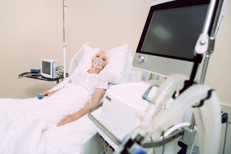Dåligt kvinna med medicinsk utrustning för hjärtahastighet som ser bildskärmen royaltyfri fotografi