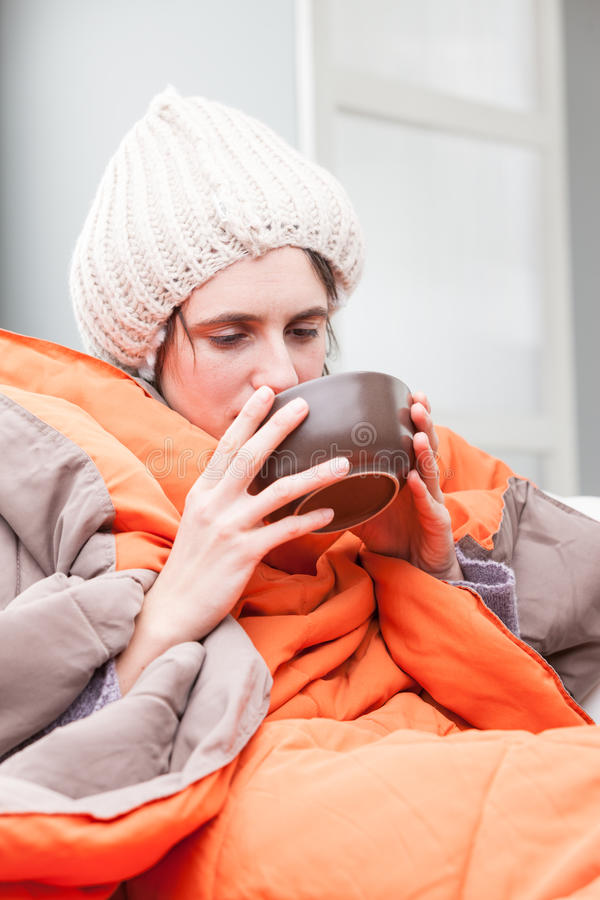 Dåligt kvinna som dricker en varm buljong arkivbild