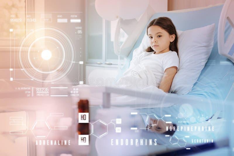 Dåligt ledsen barnkänsla, medan bli i säng i ett sjukhusrum royaltyfria foton