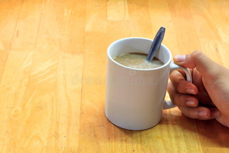 Dé alguien que lleva a cabo la taza de backgroun del café, de la cuchara y de madera de la falta de definición imagen de archivo libre de regalías