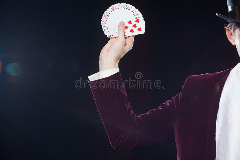 Dé con el primer de las tarjetas El Midsection de la demostración del mago avivó hacia fuera tarjetas contra fondo negro Mago, ju fotografía de archivo libre de regalías