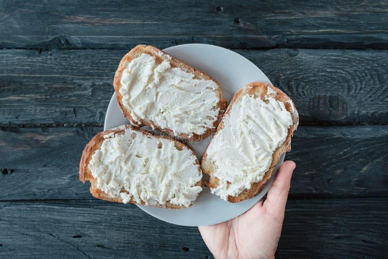 Dé a controles la placa blanca con los bocadillos hechos en casa con el queso cremoso sobre una tabla de madera negra imagenes de archivo