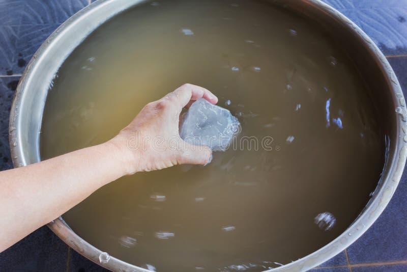 Dé el alumbre de la inmersión en agua fangosa al agua fangosa clara, a del precipitado fotografía de archivo