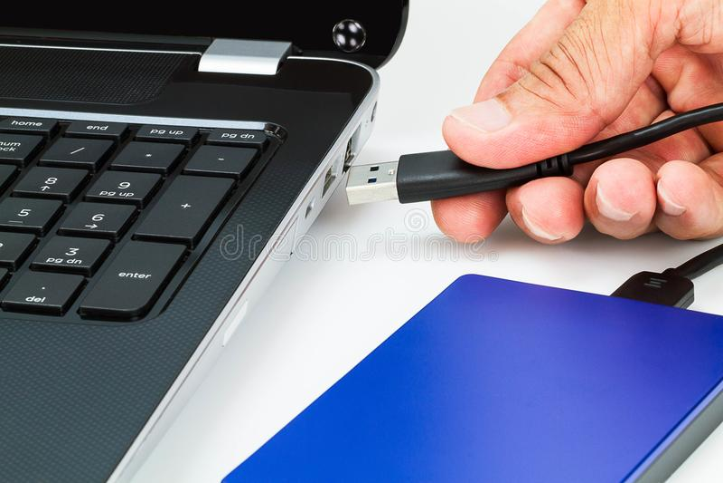 Dé el cable de conexión del usb de la unidad de disco duro externa al ordenador portátil en el escritorio blanco imagen de archivo