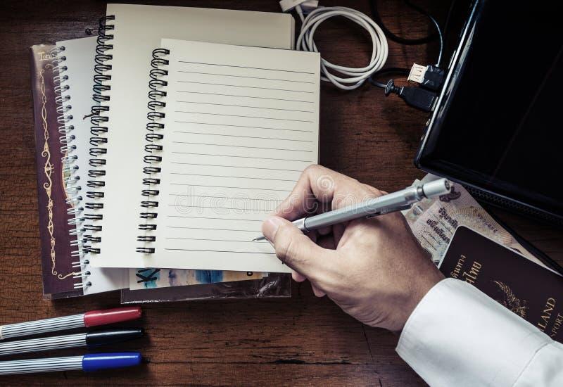 Dé el cuaderno de la pluma de tenencia de la escritura, en la tabla de funcionamiento sucia, tono del vintage imagen de archivo