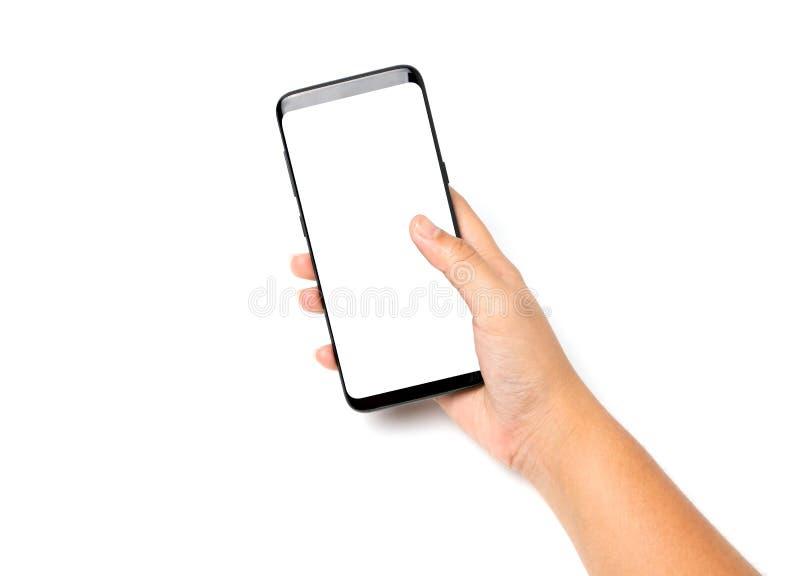 Dé el espacio en blanco del teléfono celular de tenencia en la pantalla blanca fotografía de archivo libre de regalías