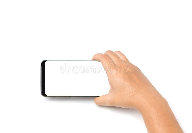 Dé el espacio en blanco del teléfono celular de tenencia en la pantalla blanca y el fondo blanco foto de archivo libre de regalías