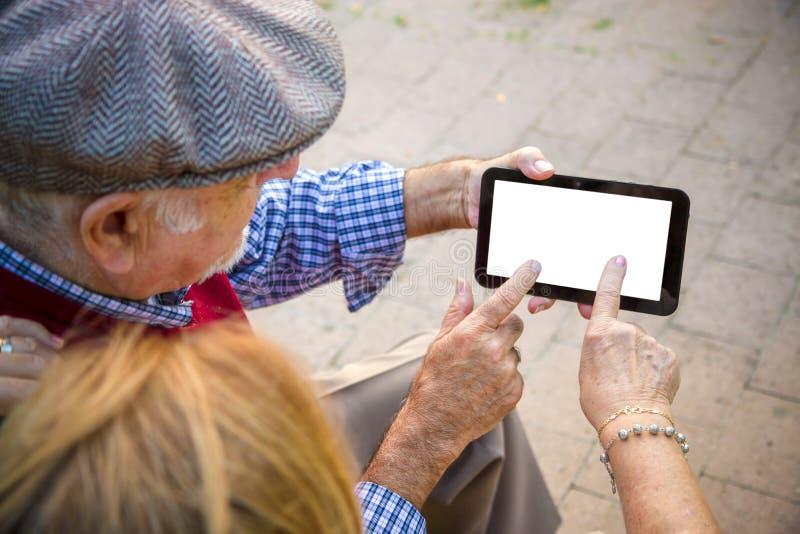 Dé el hombre mayor y la mujer que usa el teléfono celular imagen de archivo libre de regalías