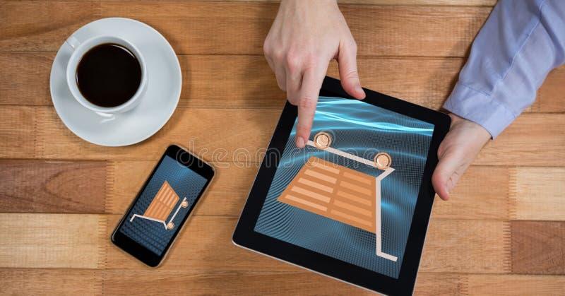 Dé el icono conmovedor del carro de la compra en la tableta por el teléfono móvil y la taza de café ilustración del vector