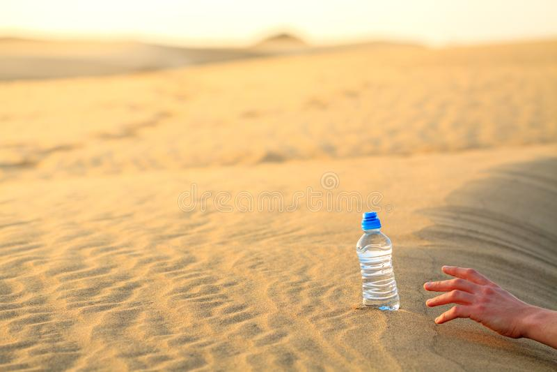 Dé el intento para coger la botella de agua en desierto de la arena fotografía de archivo libre de regalías