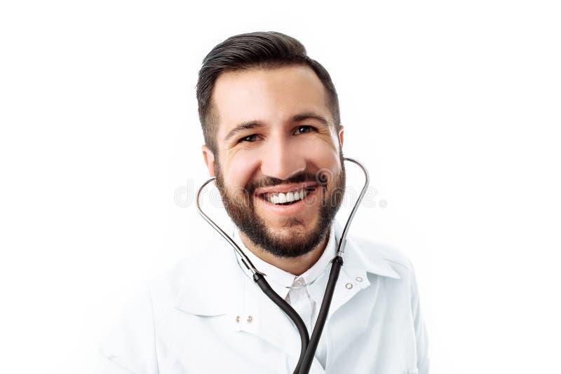 Dé el primer, sosteniendo un estetoscopio, retrato de un doctor joven, en un fondo blanco fotos de archivo libres de regalías