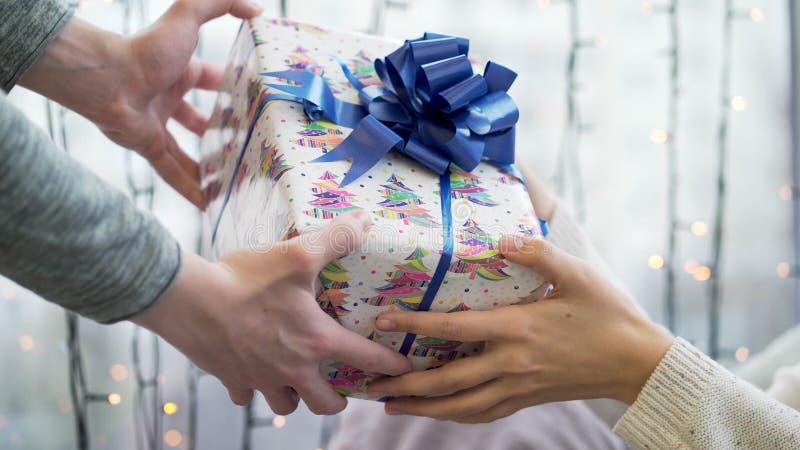 Dé el regalo Ciérrese encima de las manos de pares en el amor que da una caja de regalo Relación feliz en escena al aire libre Am foto de archivo libre de regalías