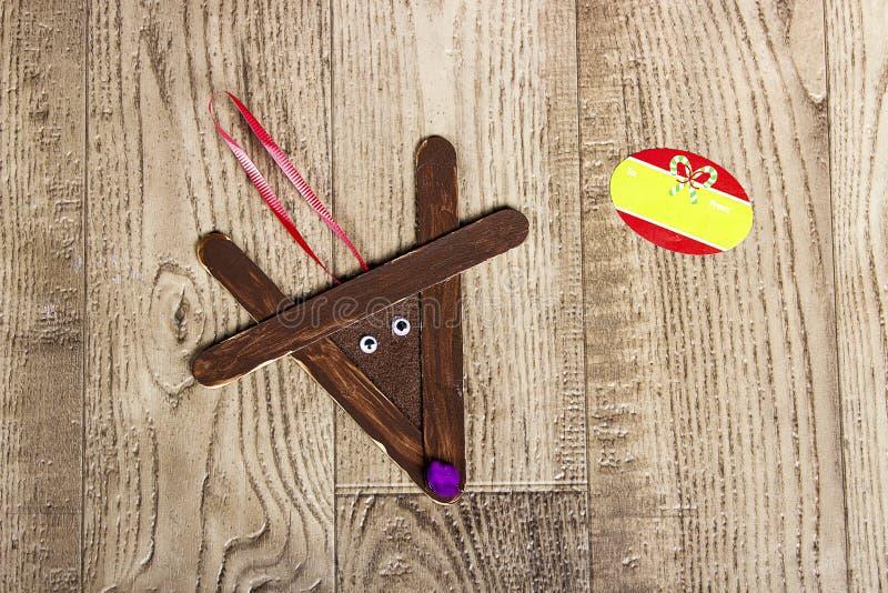 Dé el reno hecho a mano del polo, poniendo en un fondo de madera del grano fotografía de archivo libre de regalías